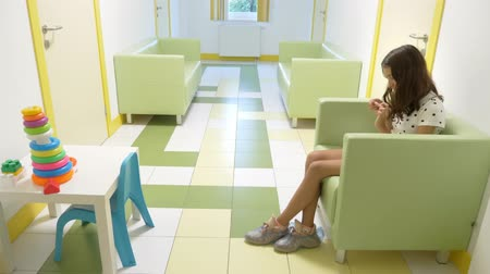 preventive : the girl is sitting in the lobby of the childrens clinic, waiting for an appointment with the doctor. concept of medical examination, health monitoring, preventive examination of doctors. Stock Footage