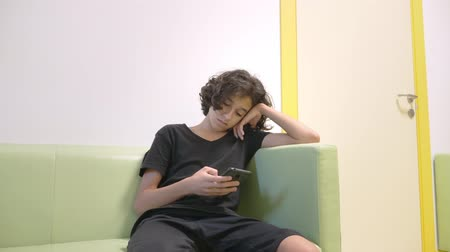 preventive : teenager boy sitting in the lobby of a childrens clinic, waiting for a meeting with a doctor , using a smartphone. The concept of medical examination, health monitoring, preventive examination of doctors.