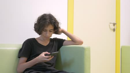 pediatria : teenager boy sitting in the lobby of a childrens clinic, waiting for a meeting with a doctor , using a smartphone. The concept of medical examination, health monitoring, preventive examination of doctors.