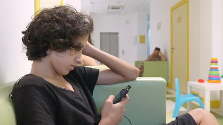 expectativa : teenager boy sitting in the lobby of a childrens clinic, waiting for a meeting with a doctor , using a smartphone. The concept of medical examination, health monitoring, preventive examination of doctors.