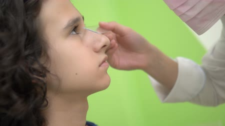 eyepieces : Ophthalmology concept, optometry. Medical ophthalmic device for eye examination. a teenager boy checks his eyesight at a doctor appointment, on equipment.