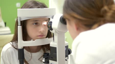 eyepieces : The concept of ophthalmology, optometry. Medical ophthalmic device for eye examination. teenage girl checks eyesight at a doctor appointment, on equipment. Stock Footage