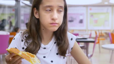 descuidado : Close-up. face teen girl eating pizza in a fast food restaurant.