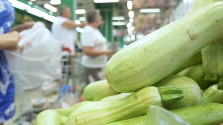 цуккини : close-up. the buyer chooses fresh zucchini in the supermarket