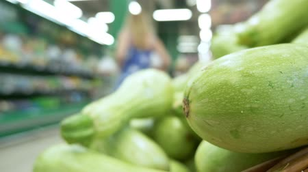 ズッキーニ : close-up. the buyer chooses fresh zucchini in the supermarket