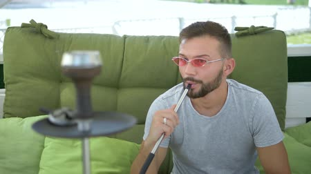 оставлять : Hookah outdoors. handsome man smokes a hookah in the gazebo on a summer sunny day