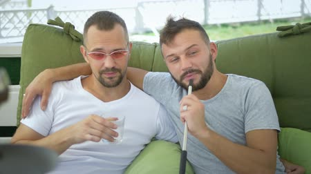 armchairs : Gay couple smokes a hookah, sitting in the gazebo on the street on a sunny summer day.