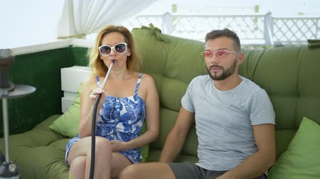 lelkesedés : couple man and woman smoke hookah in the gazebo on a clear sunny day and talk