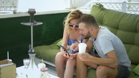 lelkesedés : couple man and woman smoke a hookah in the gazebo on a clear sunny day and use a smartphone