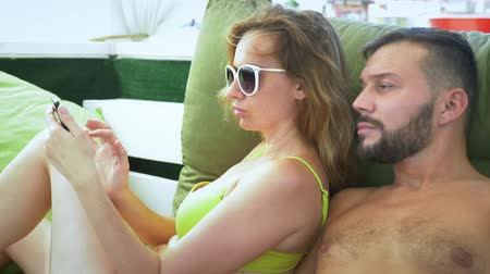 tabac : A man and a woman in a swimsuit smoke a hookah, drink cocktails in a gazebo on the beach and use a smartphone Vidéos Libres De Droits