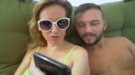 plage : A man and a woman in a swimsuit smoke a hookah, drink cocktails in a gazebo on the beach and use a smartphone Stock Footage