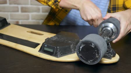 ayarlama : close-up.Man hands who repair a broken electric skateboard. unscrews the wheels Stok Video