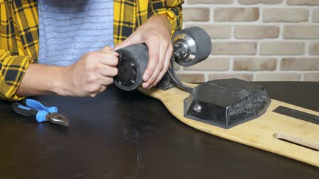 skateboard deck : close-up.Man hands who repair a broken electric skateboard. unscrews the wheels Stock Footage