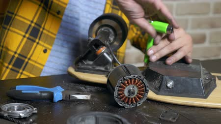 usado : close-up.Man hands who repair a broken electric skateboard. unscrews the wheels Stock Footage