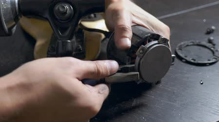 fitter : electric skate repair. close-up. locksmith unscrews the wheels on an electric skateboard.