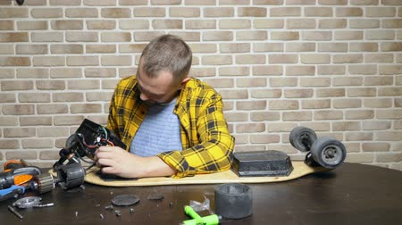 schroef : A male mechanic is repairing an electric skate sitting in a workshop in a loft. master plan Stockvideo