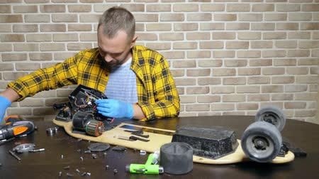 винты : A male mechanic is repairing an electric skate sitting in a workshop in a loft. master plan Стоковые видеозаписи