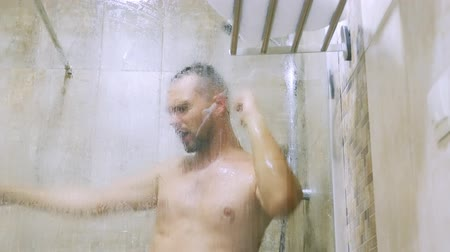 young handsome man emotionally sings and dances in the shower.