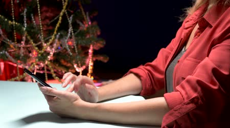 Happy New Year and Merry Christmas. close-up. female hands texting sms message on smartphone
