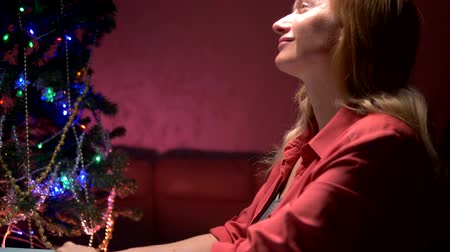 święta : woman sits at a table near a decorated Christmas tree and writes a Christmas letter to Santa Claus