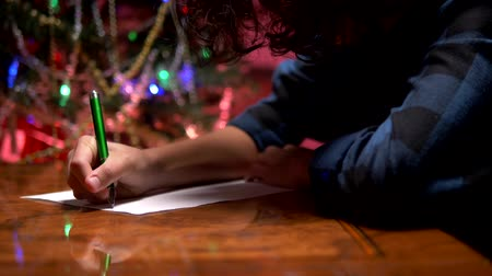 him : teen boy sits at a table near a decorated Christmas tree and writes a New Year letter to Santa Claus Stock Footage