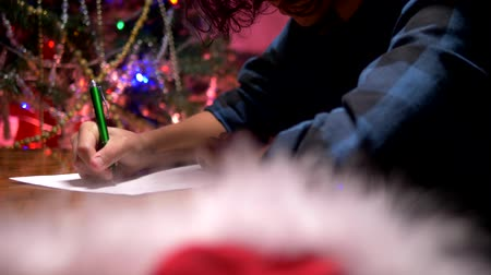 гелий : teen boy sits at a table near a decorated Christmas tree and writes a New Year letter to Santa Claus Стоковые видеозаписи