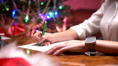 święta : business woman sits at a table near a decorated Christmas tree and writes a Christmas letter to Santa Claus