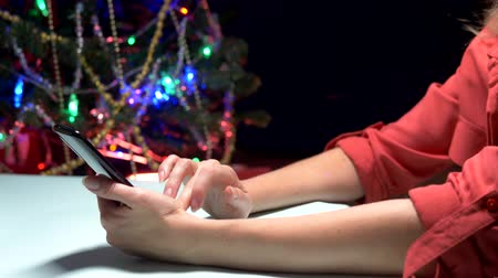 święta : Happy New Year and Merry Christmas. close-up. female hands texting sms message on smartphone