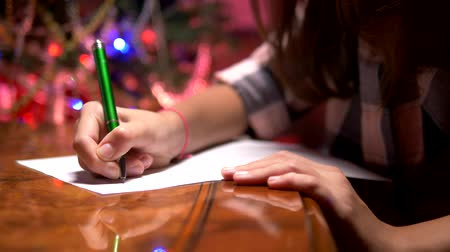święta : teen girl sits at a table near a decorated Christmas tree and writes a Christmas letter to Santa Claus