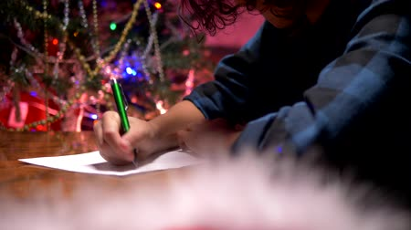 święta : teen boy sits at a table near a decorated Christmas tree and writes a New Year letter to Santa Claus Wideo