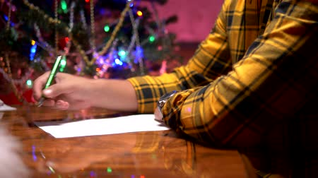 perguntando : a man sits at a table near a decorated Christmas tree and writes a New Year letter to Santa Claus