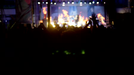 madness : blurred background, silhouettes of fans. rock concert in the evening. people in the crowd raise their hands and applaud.