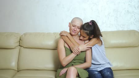 bald exhausted mother after oncology chemotherapy hugs her teenager daughter while sitting on the couch Stock mozgókép