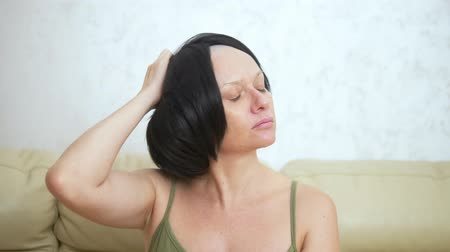 A sick, bald woman with hemotherapy removes a wig from her head.