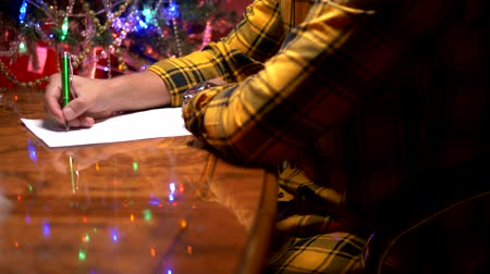 święta : a man sits at a table near a decorated Christmas tree and writes a New Year letter to Santa Claus