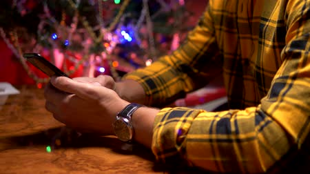 feliciteren : Happy New Year and Merry Christmas. close-up. male hands texting sms message on smartphone Stockvideo