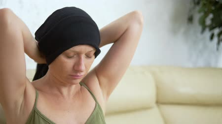 malignancy : sick woman in a headscarf sitting on a sofa. woman removes a scarf from a bald head. concept of cancer patients.