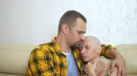 nurture : bald woman and man cuddling while sitting on a sofa. Loving couple overcome her oncology together