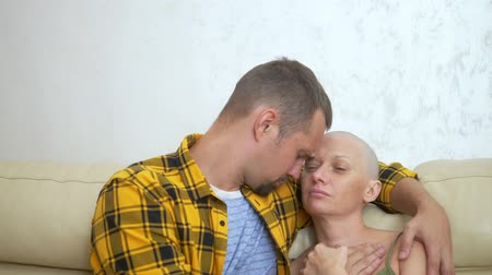 terapi : bald woman and man cuddling while sitting on a sofa. Loving couple overcome her oncology together