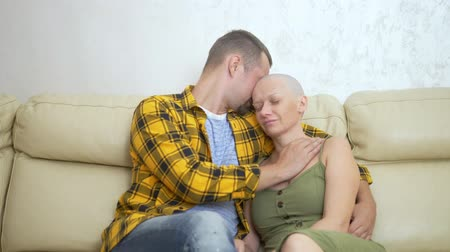 nutrir : bald woman and man cuddling while sitting on a sofa. Loving couple overcome her oncology together