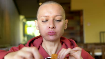 bald girl in a cafe eating a hamburger. close-up. looking at the camera