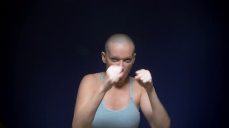bald woman boxing to the camera against a dark background