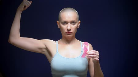 göğüs : bald woman against a dark background. healthcare, people and medicine concept - woman holding pink breast cancer awareness ribbon Stok Video