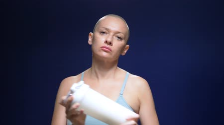 bald woman in a sports top shakes a cocktail in a shaker against a dark background.