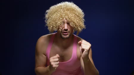 crazy handsome young guy in a curly wig and a pink t-shirt against a dark background is dancing funny, shows his muscles