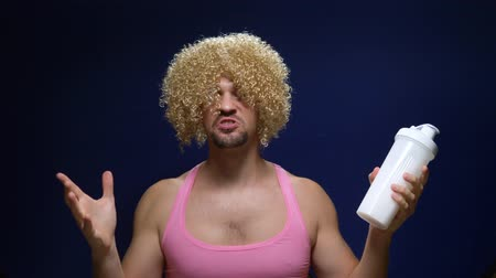 Crazy handsome guy in a curly wig and a pink T-shirt actively shakes a shaker against a dark background.