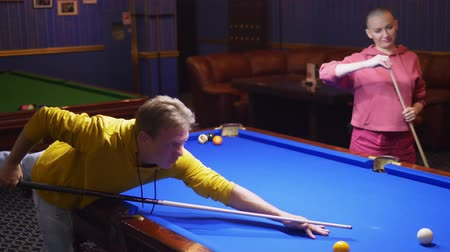 acht : couple, man and bald woman play american billiards.