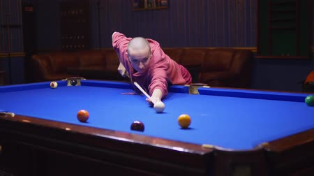 eight : beautiful bald woman plays american billiards.