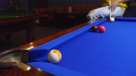 acht : young male professional pool player performing tricks while playing billiards.