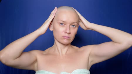 szampon : Puzzled bald woman rubs hair growth agent in her head. strange people adventure concept